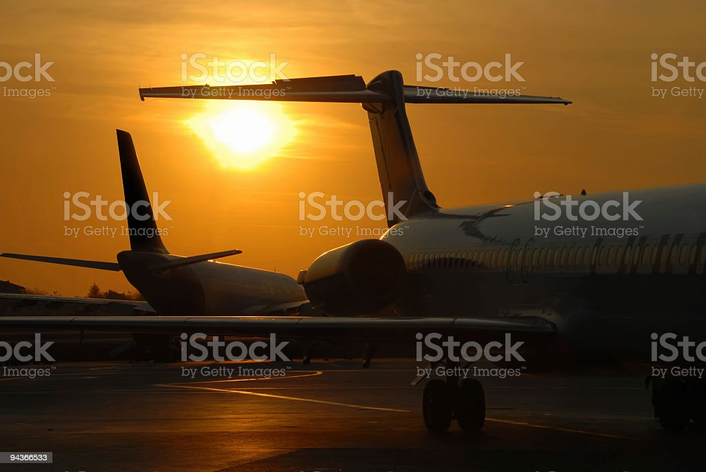 Airplane sihouettes while sunset in an airport royalty-free stock photo