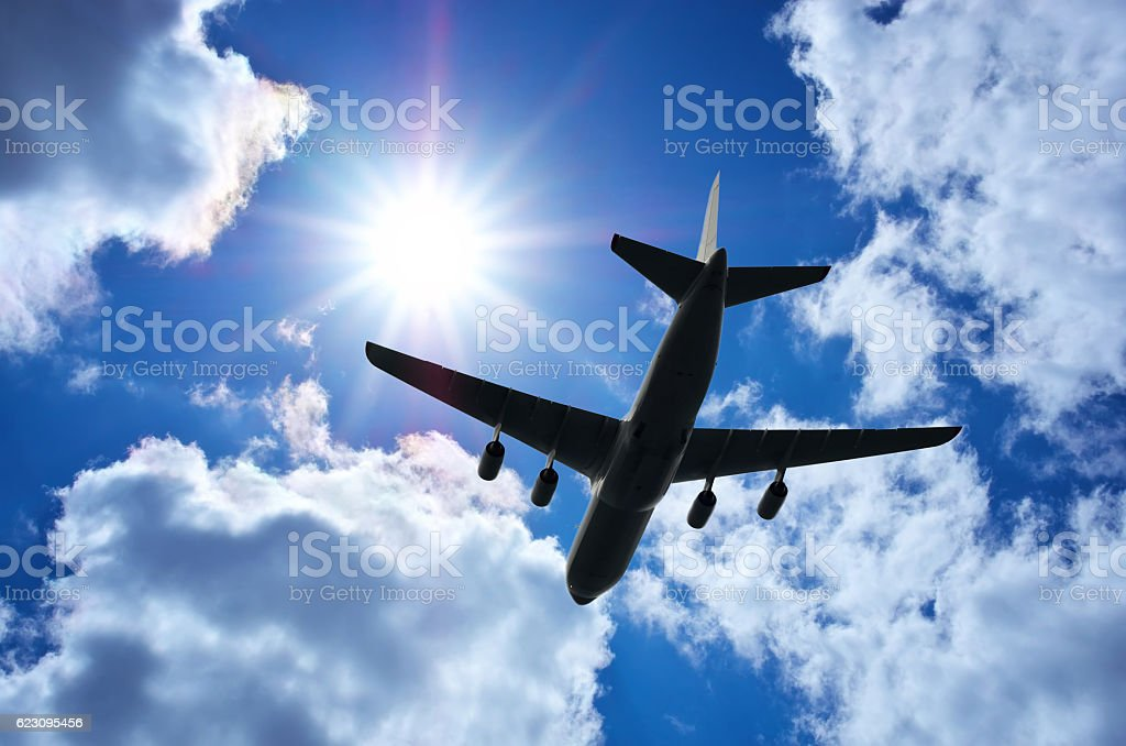 Airplane silhouette in deep blue sky. stock photo