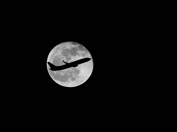 Airplane silhouette on full moon stock photo