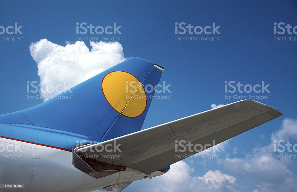 Airplane tail with clear sky and clouds stock photo