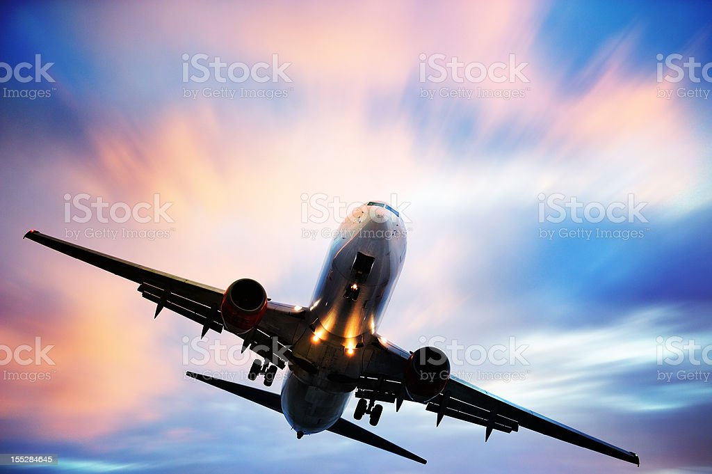 Airplane taking off against blue and pink sky stock photo