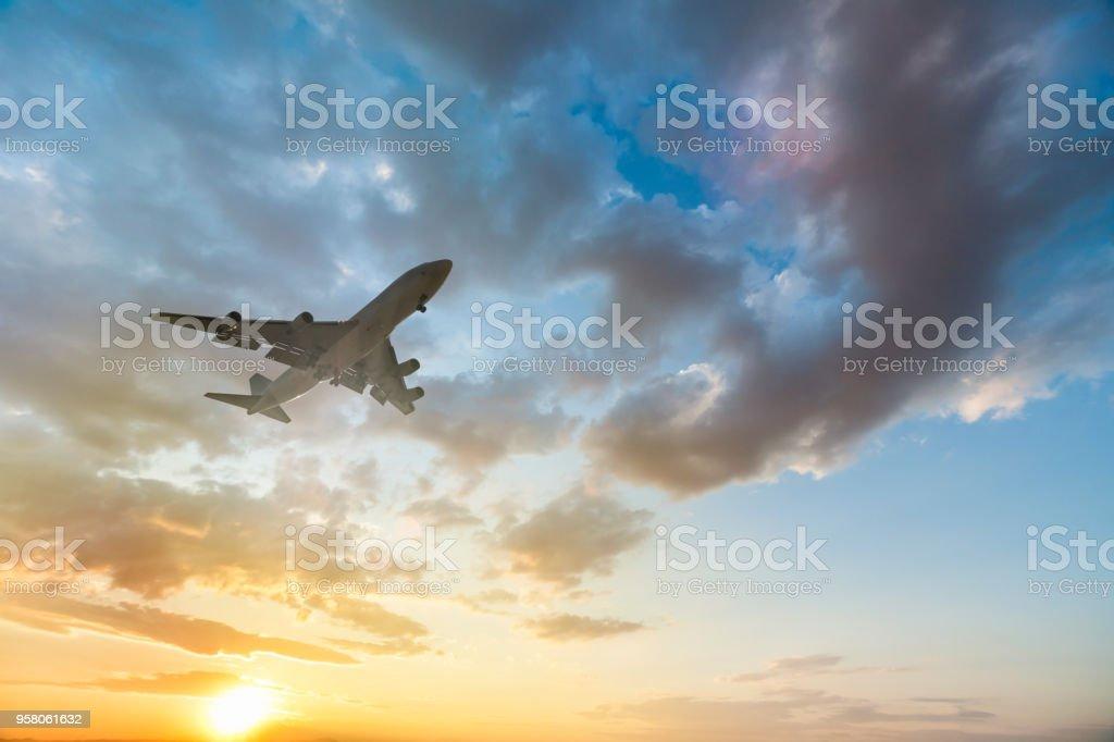 Airplane taking off at beautiful sunset stock photo