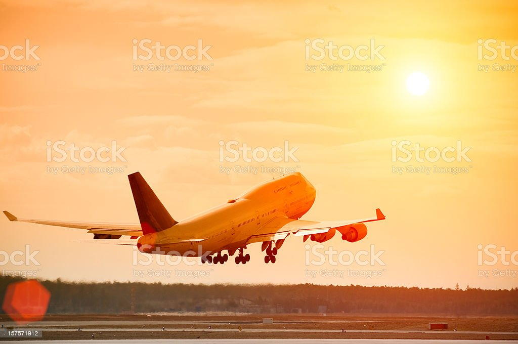 Airplane taking off at sunset, lens flare, copy space stock photo