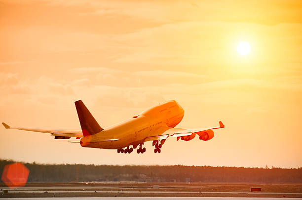 Airplane taking off at sunset, lens flare, copy space Airplane (Boeing 747-400) taking off at beautiful sunset, lens flare, orange sky, hot air evaporating from jet engines. evaporation stock pictures, royalty-free photos & images