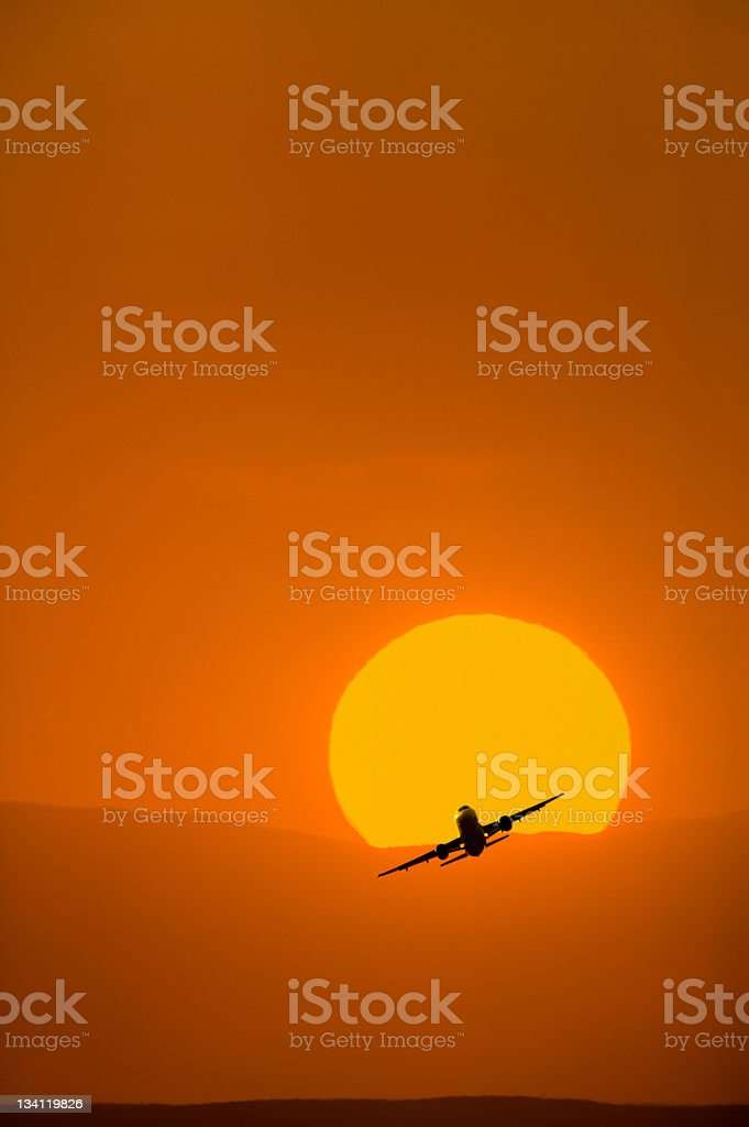 Airplane taking off with bright orange sunrise in the background royalty-free stock photo