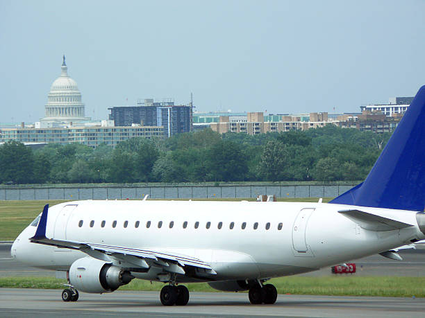 "Airplane taxiing at DCA ""Airplane taxiing for takeoff at Washington National Airport, the US Capitol in the background."" ronald reagan washington national airport stock pictures, royalty-free photos & images"