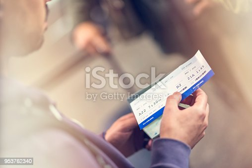 Close up of a man holing airplane ticket, blurred background.