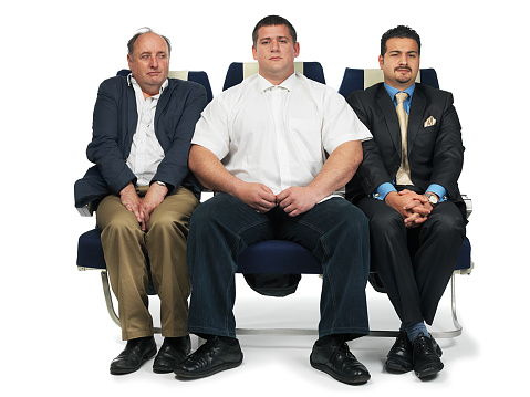 a broadman sitting on ana airplane seat leaving very little room for people beside him