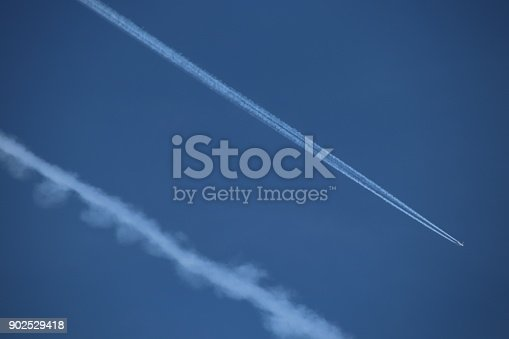589538650 istock photo Airplane trace, Vapor Trail, in the blue sky 902529418