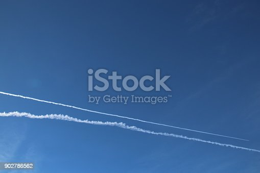 589538650 istock photo Airplane trace, Vapor Trail, in the blue sky 902786562