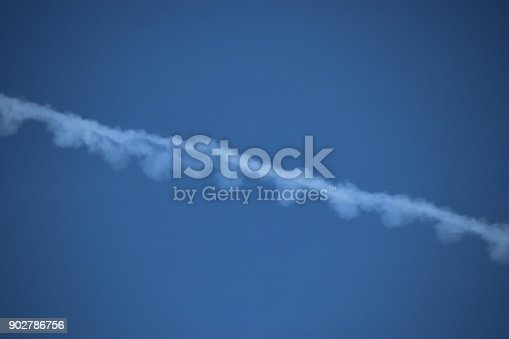 589538650 istock photo Airplane trace, Vapor Trail, in the blue sky 902786756