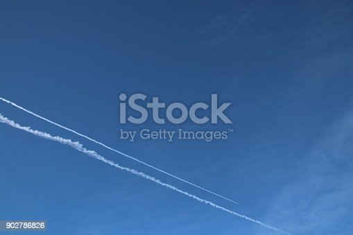 589538650 istock photo Airplane trace, Vapor Trail, in the blue sky 902786826