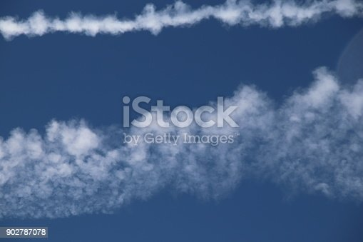 589538650 istock photo Airplane trace, Vapor Trail, in the blue sky 902787078