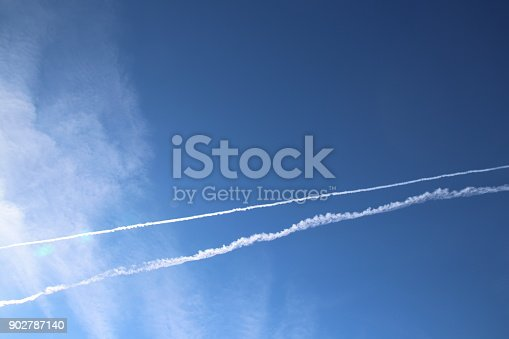 589538650 istock photo Airplane trace, Vapor Trail, in the blue sky 902787140