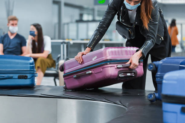 Airplane traveler wearing N95 face mask receiving luggage from conveyor belt stock photo