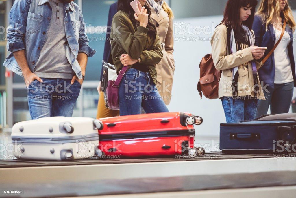 Airplane travelers waiting for luggage near conveyor belt stock photo