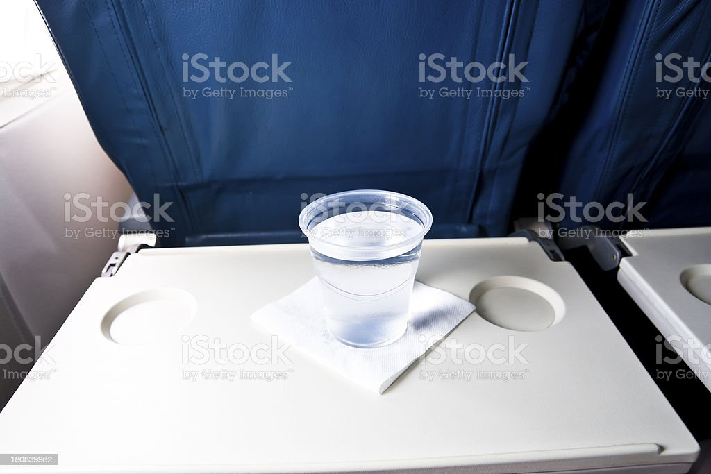 Airplane tray table with a cup of water stock photo