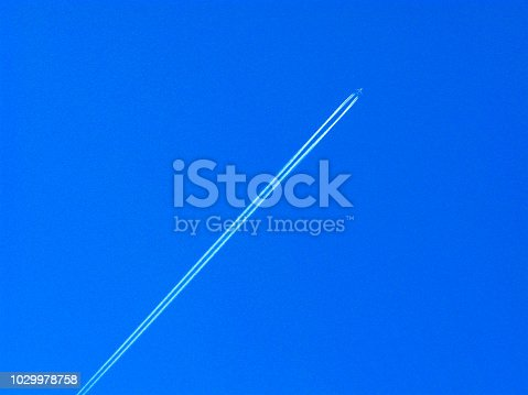 istock Airplane upwards and vapour trail on blue sky 1029978758