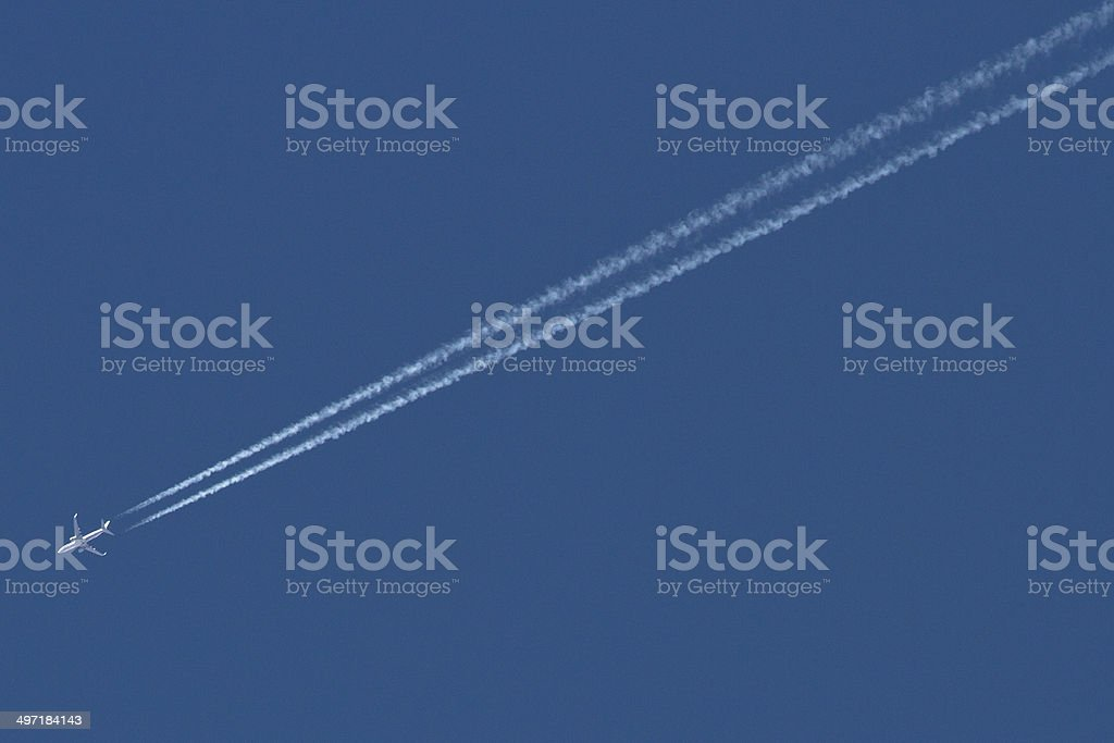 Airplane vapor trails left in the sky stock photo
