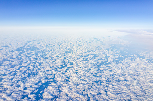 621114928 istock photo Airplane window view of blue clear sky high angle above over Atlantic ocean during sunny day and pattern of clouds by horizon 1217469101