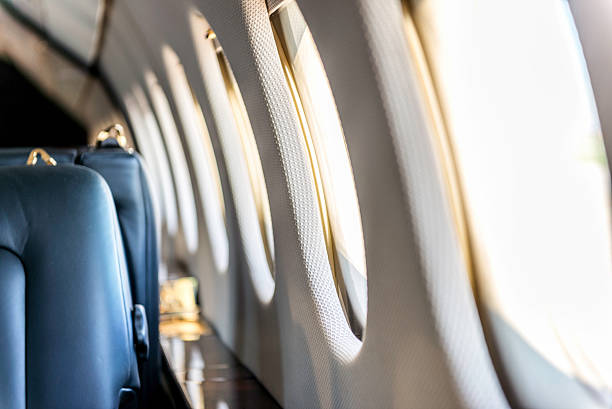 Airplane windows Close-up of a luxury airplane windows in a row. Interior of private jet, no people image, space for copy. military private stock pictures, royalty-free photos & images