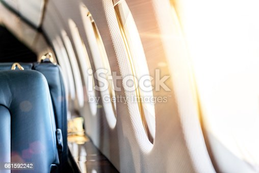 Horizontal color close-up image of a luxury airplane windows with sunbeams in a row. Interior of private jet, no people image, space for copy.