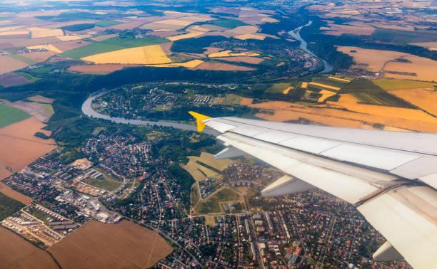 Flugzeugfenster blicke über der Erde auf Wahrzeichen nach unten. Blick von einem Flugzeugfenster über einen Flügel, der hoch über Ackerland und Feldern fliegt. Blick aus dem Fenster des Flugzeugfliegens. – Foto