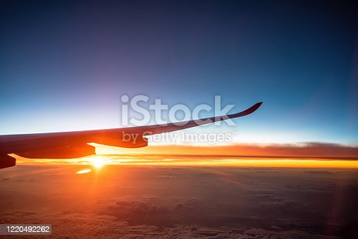 925925874 istock photo Airplane wing above beautiful sunrise sky (view from airplane) 1220492262