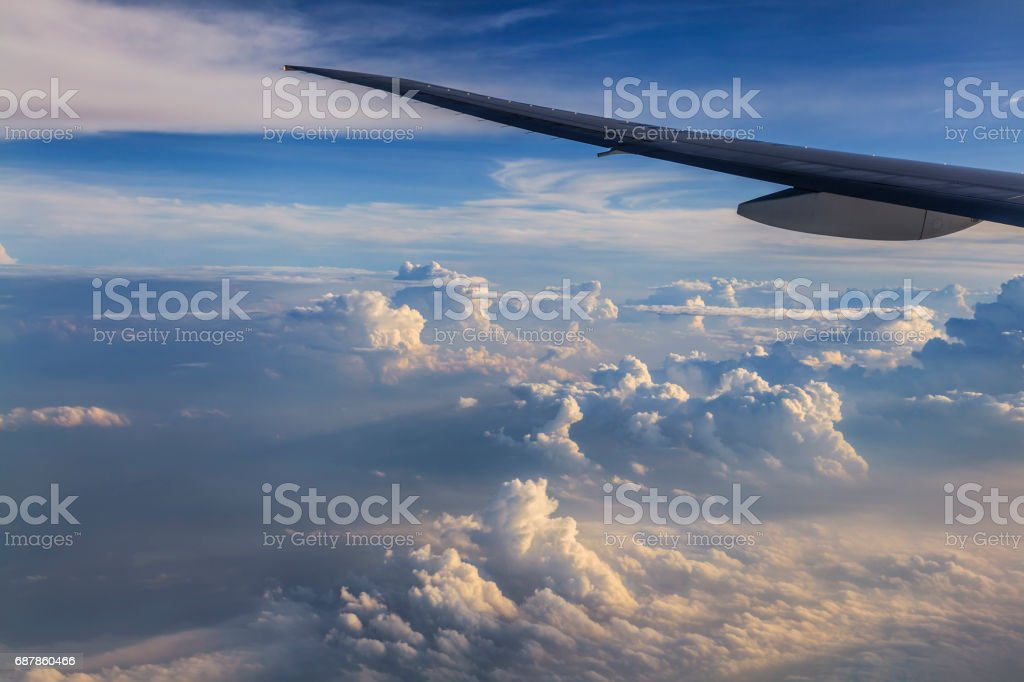Airplane wing against a background of clouds. View from the wind stock photo