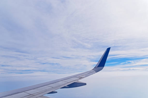 Airplane wing against cloudy sky stock photo