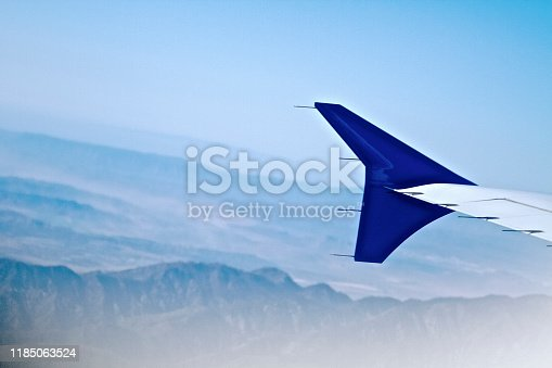 istock Airplane Wing against mountain backgrounds 1185063524