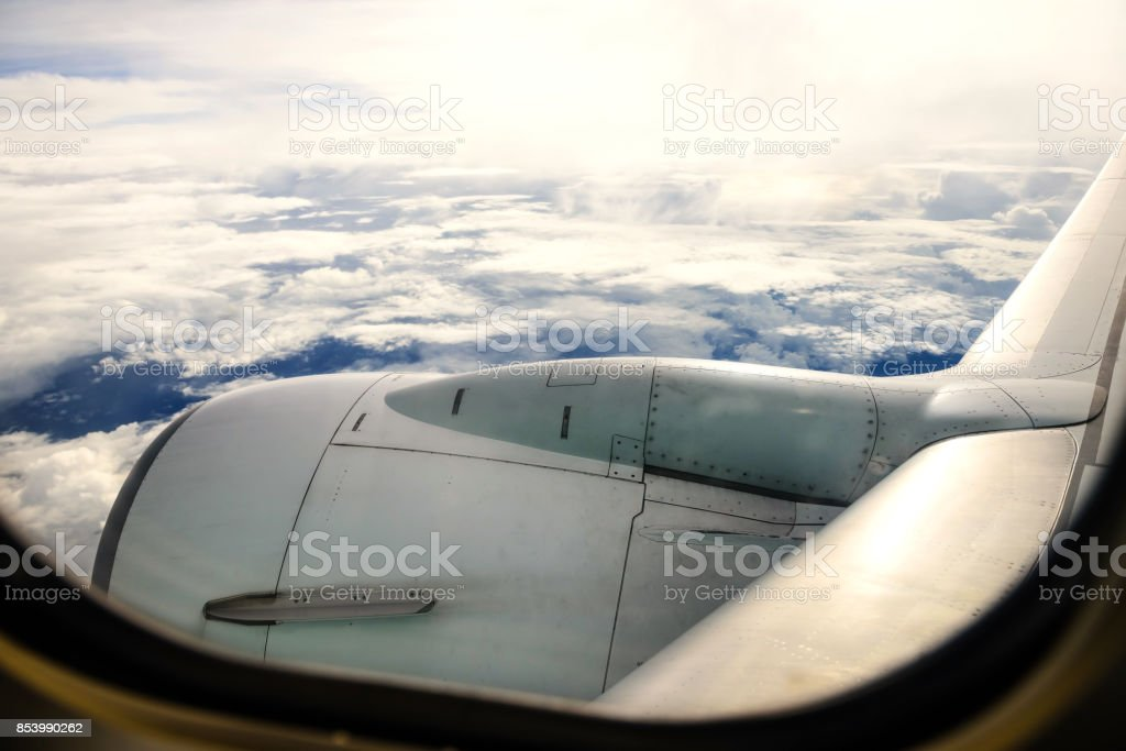 airplane wing against sky and clouds by the view of aircraft window. Transportation and travel stock photo
