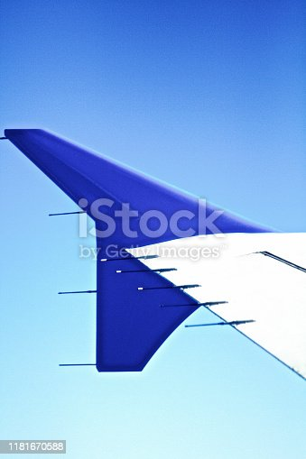 istock Airplane Wing against vibrant blue sky background 1181670588