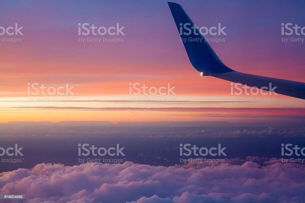 Airplane wing at sunset over the clouds. stock photo