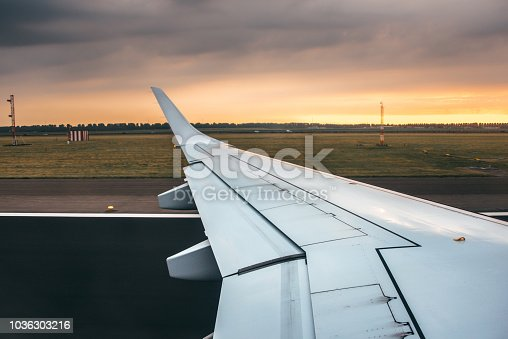 484616224 istock photo Airplane wing at sunset 1036303216