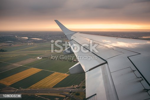 484616224 istock photo Airplane wing at sunset 1036303236
