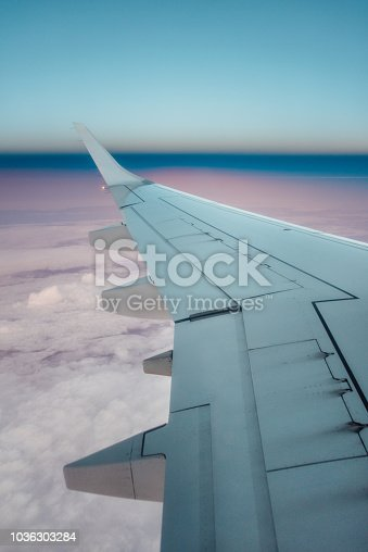 484616224 istock photo Airplane wing at sunset 1036303284