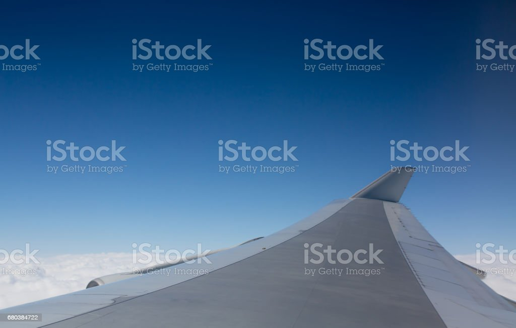 Airplane Wing Flying Above Clouds. Plain Blue Sky Background royalty-free stock photo