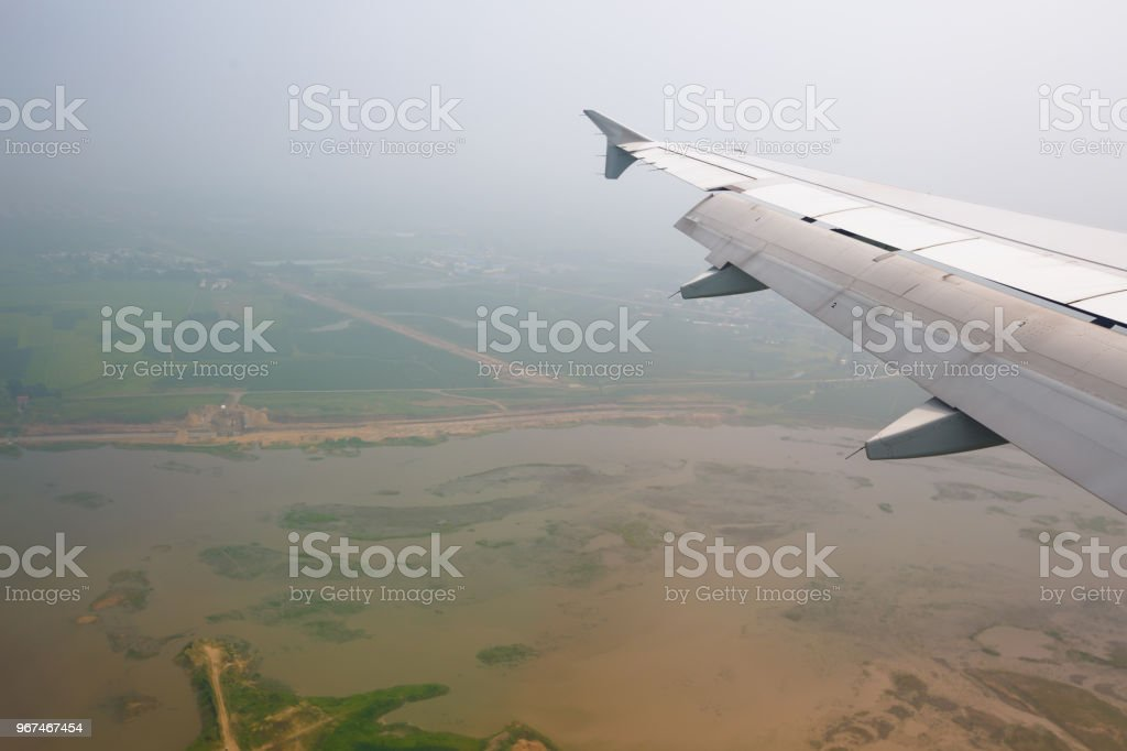 Airplane wing flying above green fields