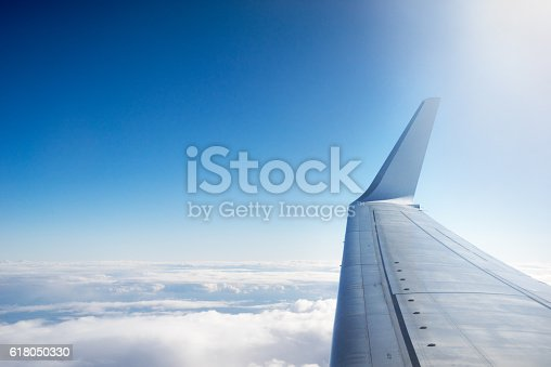 902818356 istock photo Airplane wing flying above the clouds 618050330