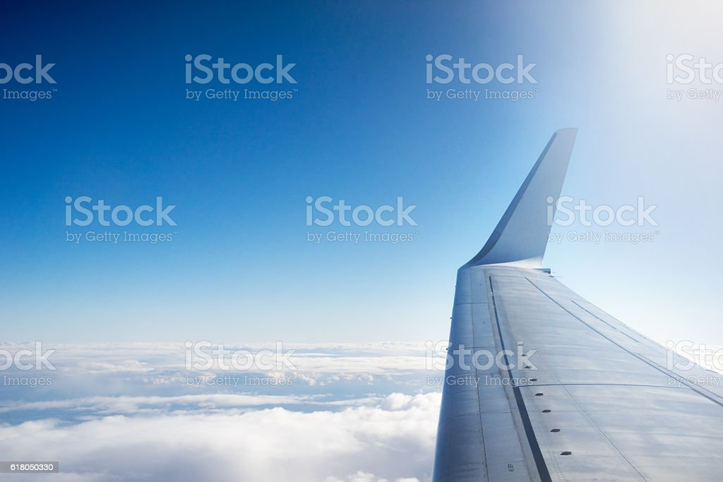 Airplane wing flying above the clouds stock photo