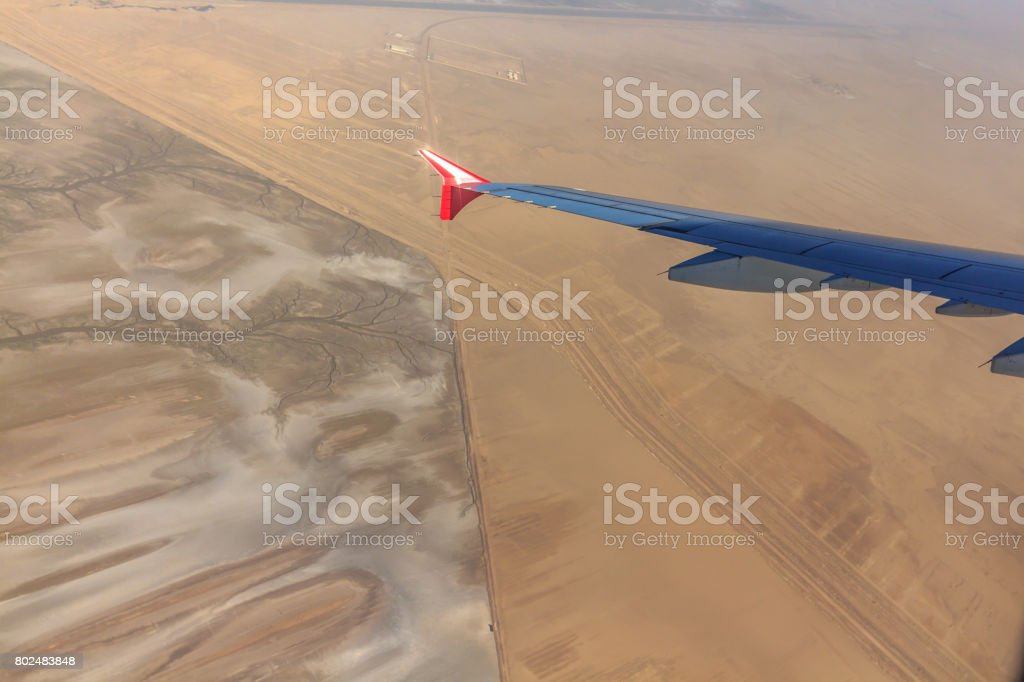 Airplane wing flying above the desert stock photo