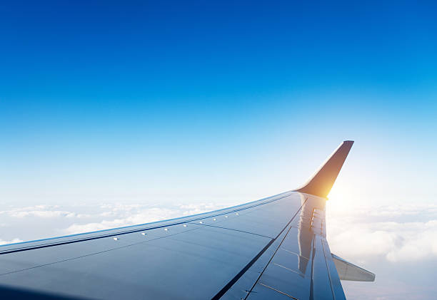 Airplane wing in flight above clouds stock photo