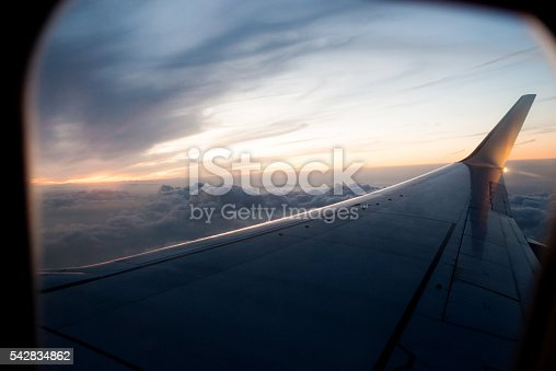 Airplane wing in flight at sunset.