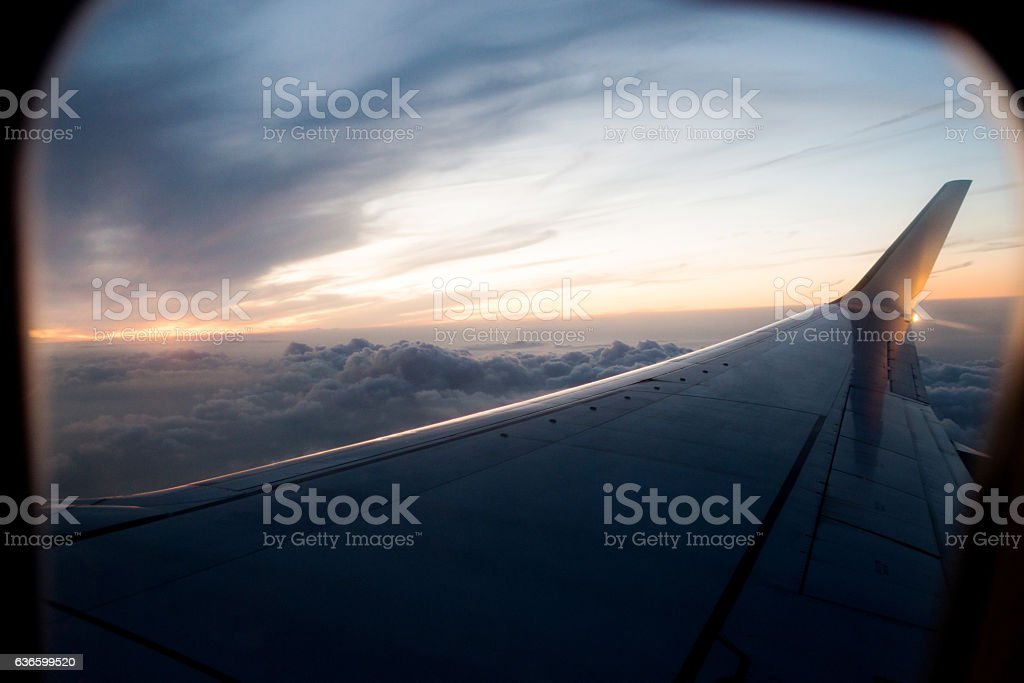 Airplane wing in flight at sunset stock photo