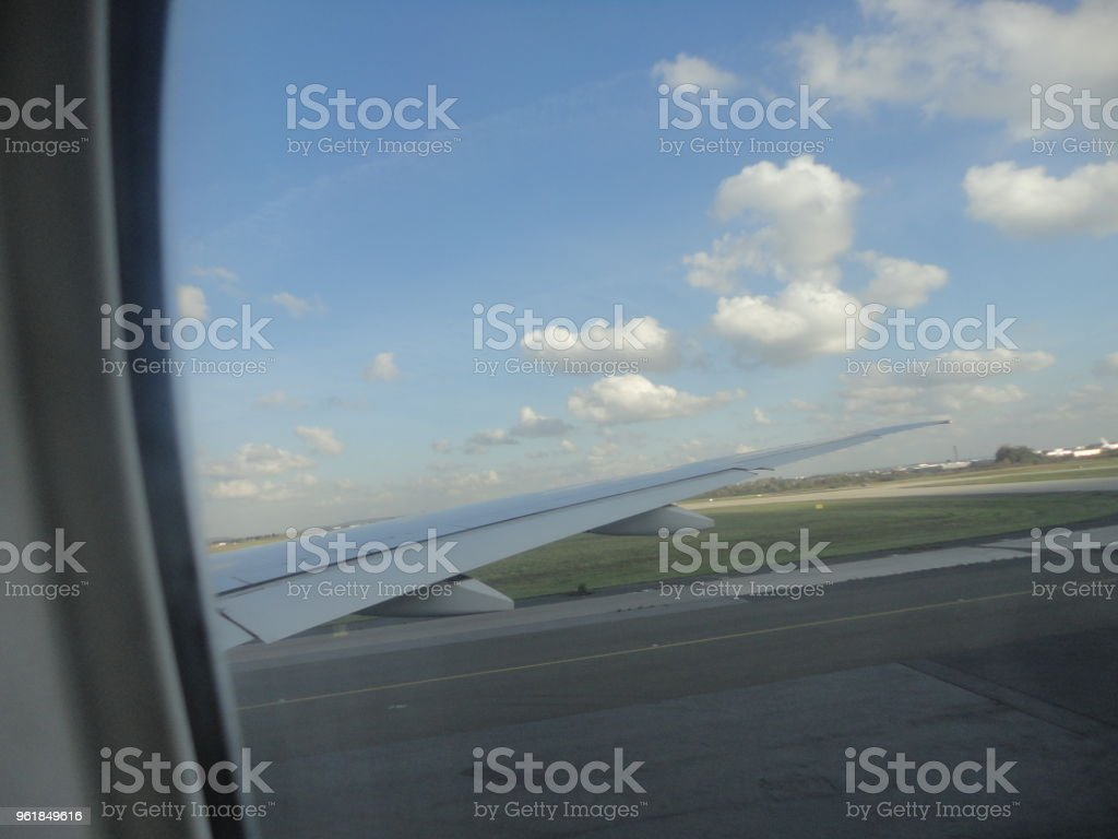 Airplane Wing in Flight from window, Airport Runway. stock photo