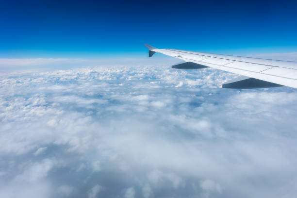 Airplane Wing in Flight from window, cloudy sky stock photo