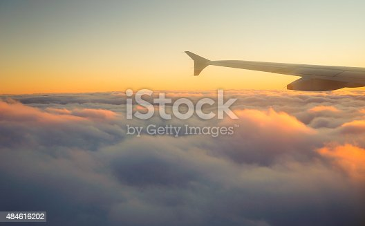 484616224 istock photo Airplane Wing in Flight from window, sunset sky 484616202
