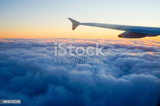 484616224 istock photo Airplane Wing in Flight from window, sunset sky 484616208