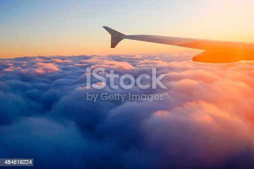 istock Airplane Wing in Flight from window, sunset sky 484616224